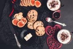 Café da manhã romântico duas xícaras de café, cappuccino com cookies do chocolate e biscoitos perto dos corações vermelhos no fun Imagem de Stock Royalty Free