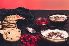 Café da manhã romântico duas xícaras de café, cappuccino com cookies do chocolate e biscoitos perto dos corações vermelhos no fun Fotografia de Stock