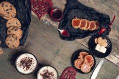 Café da manhã romântico duas xícaras de café, cappuccino com cookies do chocolate e biscoitos perto dos corações vermelhos no fun Foto de Stock Royalty Free