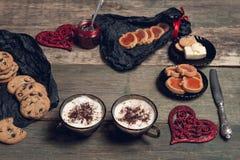 Café da manhã romântico duas xícaras de café, cappuccino com cookies do chocolate e biscoitos perto dos corações vermelhos no fun Fotos de Stock