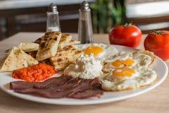 Café da manhã sérvio com pão dos ovos, do presunto, do queijo, o ajvar e o caseiro Imagens de Stock Royalty Free