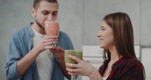 Café da manhã da saúde para um batido bebendo dos pares novos do vegetariano na manhã de um vidro grande em um moderno bonito vídeos de arquivo