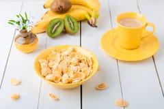 Café da manhã saudável com flocos do cereal e fruto perto do vaso com as flores no fundo branco Imagens de Stock