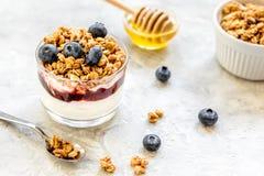Café da manhã saudável do iogurte com muesli e das bagas na mesa de cozinha Fotografia de Stock