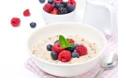 Café da manhã saudável - farinha de aveia com as bagas frescas isoladas no branco fotografia de stock