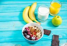 Café da manhã saudável - farinha de aveia com frutos, leite e suco na tabela azul Imagem de Stock