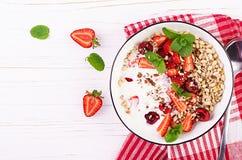 Café da manhã saudável - granola, morangos, cereja, porcas e iogurte em uma bacia em uma tabela de madeira imagem de stock