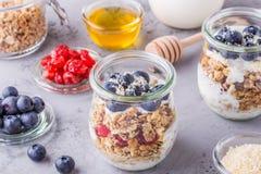 Café da manhã saudável - os frascos de vidro da aveia lascam-se com fruto fresco Imagens de Stock