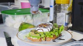 Café da manhã saudável que faz um sanduíche com ovo frito e abacate Derramando o molho video estoque