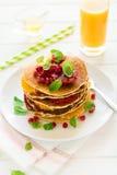 Café da manhã tradicional: a pilha de panquecas com fatias e as sementes alaranjadas da romã decorou as folhas de hortelã fotografia de stock