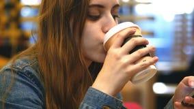 Café da manhã - uma jovem mulher aprecia cheirar e sorver uma xícara de café video estoque