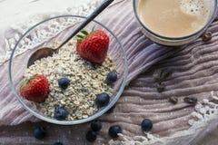 Café da manhã usual: rolam com cereais e as bagas e a xícara de café no tecido cor-de-rosa na luz do dia Imagens de Stock Royalty Free