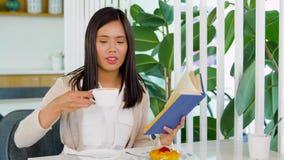 Café da mulher e livro de leitura bebendo no café video estoque