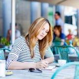 Café da mulher e notas bebendo da escrita no café Fotos de Stock Royalty Free