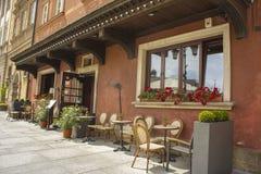 Café da rua Tabelas, cadeiras, flores em uns potenciômetros Imagem de Stock