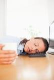 Café da terra arrendada da mulher de negócios do sono no escritório Foto de Stock
