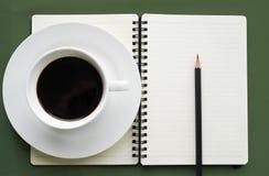 Café dans la tasse blanche avec le livre et le crayon de journal Photo stock