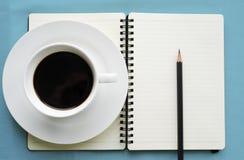 Café dans la tasse blanche avec le livre et le crayon de journal Image libre de droits