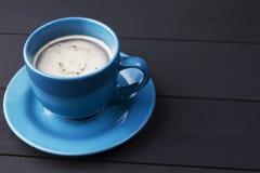 Café dans la tasse bleue avec le plat assorti sur le fond en bois noir image stock