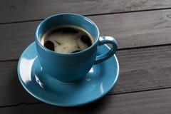 Café dans la tasse bleue avec le plat assorti sur le fond en bois noir images libres de droits