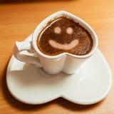 Café dans la tasse en forme de coeur avec le signe de visage de sourire Photo libre de droits
