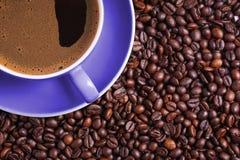 Café dans la tasse pourpre sur la table entourée avec des grains de café photos stock