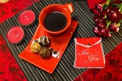 Café dans la tasse rouge avec l'enveloppe de cadeau Photographie stock libre de droits