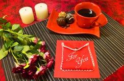 Café dans la tasse rouge avec l'enveloppe de cadeau Photos libres de droits