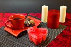 Café dans la tasse rouge et un présent sous forme de coeur Images stock