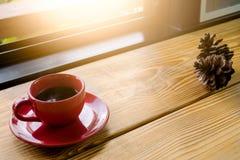 Café dans la tasse rouge sur la planche dans la lumière de matin Images libres de droits
