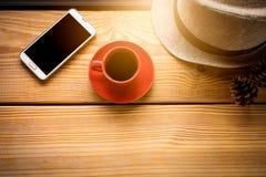 Café dans la tasse rouge sur la planche dans la lumière de matin Image stock