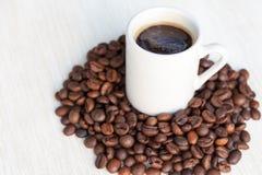 Café dans la tasse sur des haricots Photographie stock libre de droits