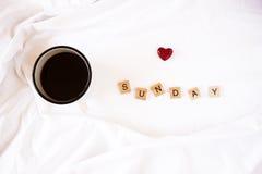 Café dans le lit et les lettres en bois Photographie stock libre de droits