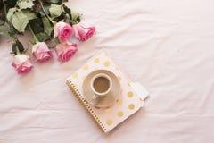 Café dans le lit sur les feuilles roses Roses, carnets autour Espace de travail indépendant de féminité de maison de mode Photographie stock libre de droits