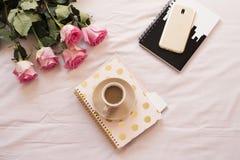 Café dans le lit sur les feuilles roses Roses, carnets, smartphone d'or autour Espace de travail indépendant de féminité de maiso Image stock