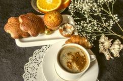 Café dans les plats blancs de tasse et soucoupe avec les gâteaux et le chocolat Photographie stock libre de droits