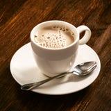 Café dans un plat de porcelaine blanc sur le vieux conseil images libres de droits