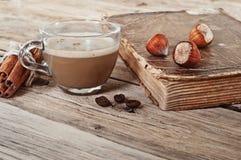 Café dans une tasse de verre avec le livre de vintage Photographie stock libre de droits