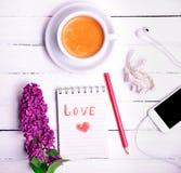 Café dans une tasse ronde blanche avec un carnet Images stock