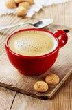 Café dans une tasse rouge un conseil en bois rustique Photos stock