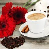 Café dans une tasse sur une soucoupe avec des bâtons de cannelle Images libres de droits