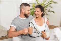 Café de abarcamiento y de consumición de los pares jovenes mientras que se sienta en casa Foto de archivo