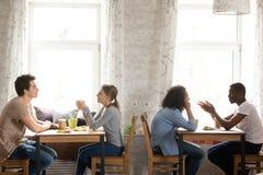Café de assento e bebendo dos povos multirraciais novos no café acolhedor foto de stock