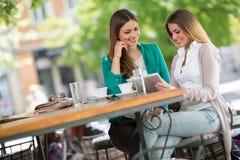 Café de boissons d'amies et comprimé numérique d'utilisation Photos stock