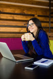 Café de boissons de jeune dame à son espace de fonctionnement dans le bureau moderne Photographie stock libre de droits