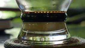 Café de brassage avec du lait utilisant un filtre traditionnel vietnamien de phin en café Les égouttements de café chute lentemen banque de vidéos