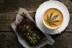 Café de cannabis - feuille de marijuana sur la mousse de café photographie stock