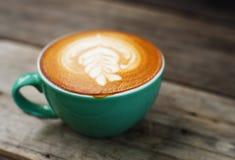 Café de cappuccino dans une tasse verte sur en bois Photos stock