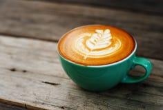 Café de cappuccino dans une tasse verte sur en bois Photographie stock