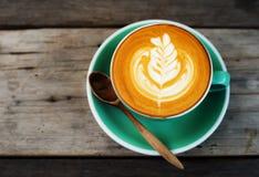 Café de cappuccino dans une tasse verte sur en bois Images libres de droits